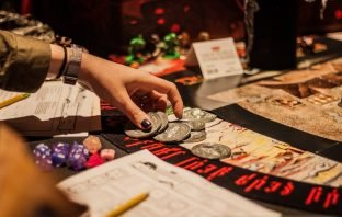 Hand reaches to table to pick up soul coins