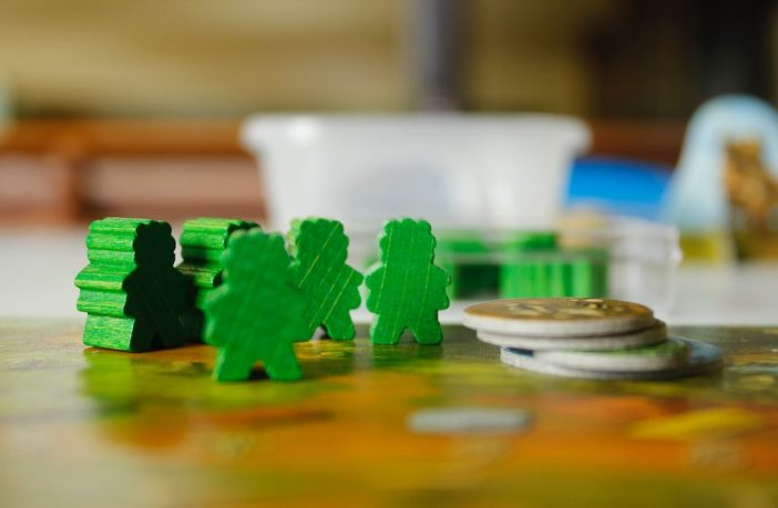 Wooden meeple figures on a boardgame