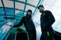 Two people on an escalator wearing Raxer tracksuits and the Razor Project Hazel smart mask. One appears to be visibility questioning the lift choices that lead them to this moment.